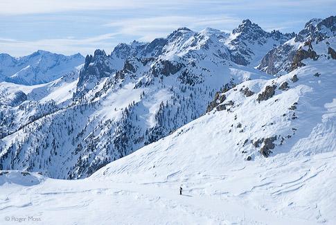Skier on piste above mountain backdrop