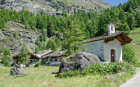 Tiny chapel, with chalets behind, in a sheltered clearing with trees and mountainsides.