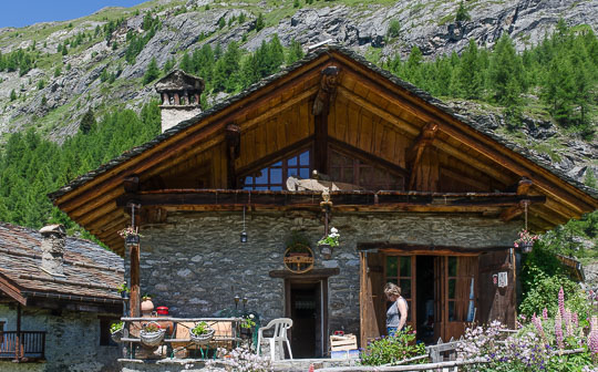 Exterior of chalet-style cafe, showing larch roof timbers and restored stonework.
