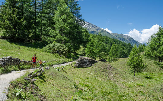 Visitors walking towards the village, showing the beauty of the mountain landscape.
