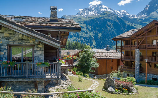 Stone chalets in the heart of the ski village, with summer flower displays and a mountain backdrop.